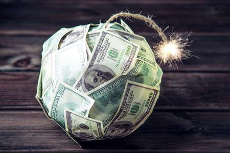 Große Bombe des Geldes hundert Dollarscheine mit einem brennenden Docht. Kurz vor der Explosion. Das Konzept der Finanzkrise Standard-Bild - 92625649