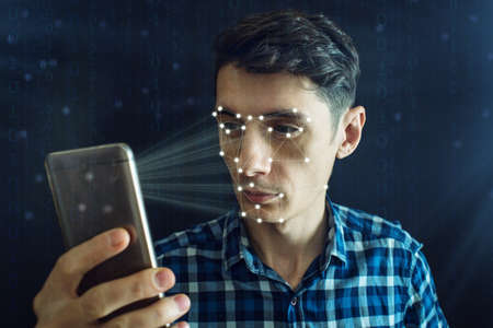 Man is trying to access the phone using the personal identification method of face recognition according to the polygonal mesh. The concept of modern technology Banque d'images