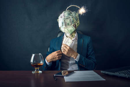 A businessman sitting on the workplace and putting the bribe money in his pocket with a bomb in the form of a ball dollar bills instead of his head. The concept of risk of financial fraud.