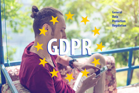 General Data Protection Regulation GDPR . The text with the EU flag in the background a man uses a mobile phone Stok Fotoğraf