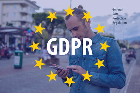 General Data Protection Regulation GDPR . The text with the EU flag in the background a man uses a mobile phone Stockfoto