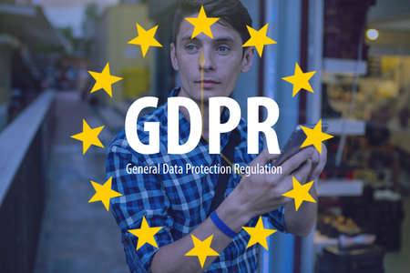 General Data Protection Regulation GDPR . The text with the EU flag in the background a man uses a mobile phone Archivio Fotografico