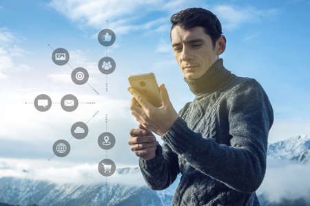 A man uses a smartphone to access social digital media in the Internet: shopping, entertainment, search and file storage. The concept of a global network expansion