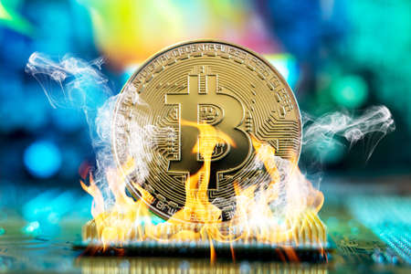 Bitcoin cryptocurrency in the form of a coin burns on fire on a microchip. The concept of death blockchain and a drop in prices Stock Photo