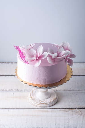 Beautiful pink wedding cake decorated with flowers. The concept of elegant holiday desserts