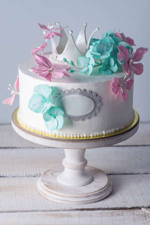 Beautiful white cake decorated with pink and turquoise flowers and a Princess crown. The concept of elegant holiday desserts for girls birthday party Archivio Fotografico - 96081679