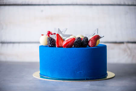 Beautiful blue cake decorated with strawberries and BlackBerry on top