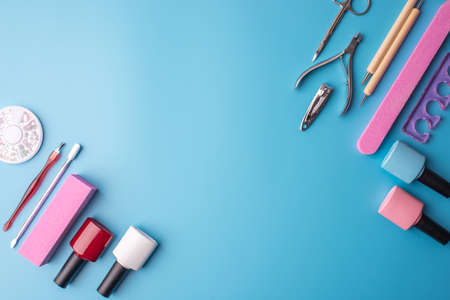 A set of cosmetic tools for manicure and pedicure on a blue background. Gel polishes, nail files and clippers, and the lamp top view