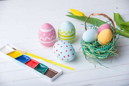 Colorful bright Easter eggs with paints hand painted on a white wooden background. Festive spring card