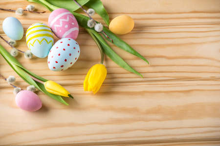 Colorful bright Easter eggs with yellow Tulip hand painted on a light wooden background. Festive spring card