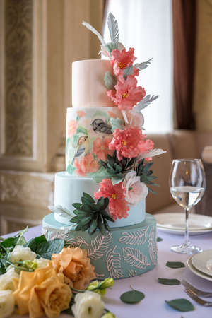 A beautiful home wedding for-tiered cake on the table in the restaurant decorated with pink roses and green leaves in a rustic style. celebratory Banquet