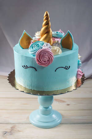 A beautiful bright cake decorated in the form of fantasy unicorn in the blue bookcase. The concept of a festive dessert for kids birthday