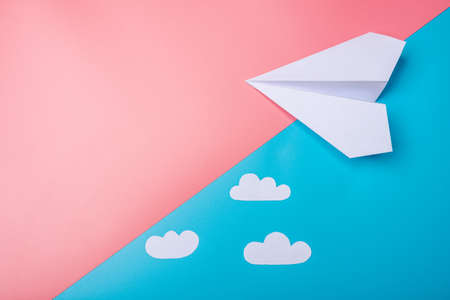 White Paper Origami Airplane With Clouds Lies On Pastel Blue Stock
