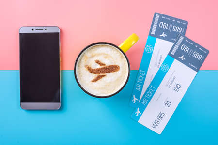 Coffee cappuccino with a picture of the airplane on the foam, top view. Pastel bright background. The concept of air travel.