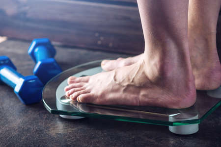 Female feet standing on electronic scales for weight control with dumbbells on dark background. The concept of sports training, diets and weight loss Standard-Bild - 100049090