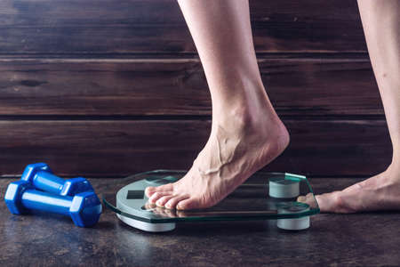 Female feet standing on electronic scales for weight control with dumbbells on dark background. The concept of sports training, diets and weight loss