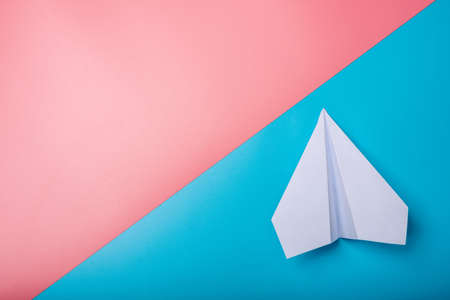 White paper origami airplane lies on pastel colors background, top view.