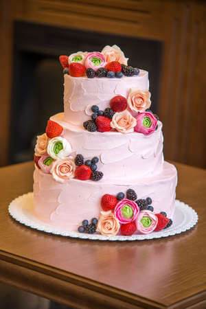 Beautiful elegant three tiered pink wedding cake decorated with berries and flowers. The concept patisserie floristic from sugar mastic