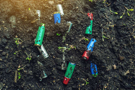 Used alkaline batteries lie in the soil where plants grow. The concept of environmental pollution with toxic household waste 版權商用圖片 - 100539163