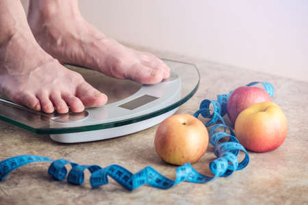 Female feet standing on electronic scales for weight control with measuring tape and apples on light background. The concept of sports training, diets and weight loss