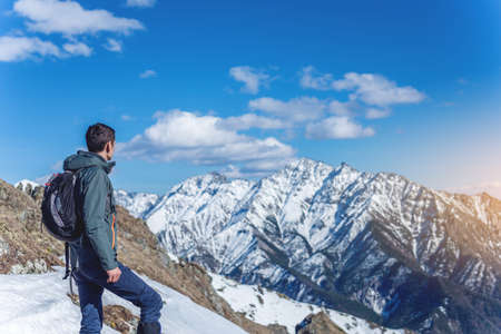Man Hiker stands on top and looks up at the sky and snowy mountains around in Sunny weather. The concept of travel and achieve the goal Stock Photo - 101864637