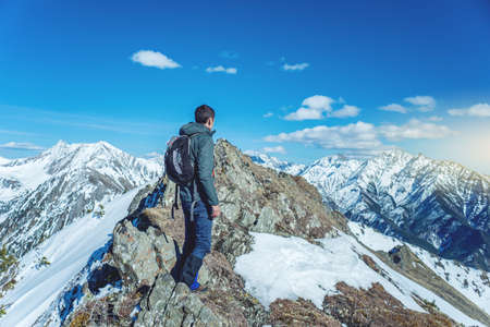 Man Hiker stands on top and looks up at the sky and snowy mountains around in Sunny weather. The concept of travel and achieve the goal Stock Photo
