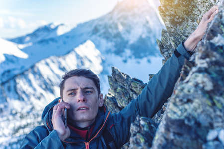 A young man climbs the mountain to the top and talking holding the phone in his hand. The concept of persistence and goal achievement in your career. Work in difficult conditions