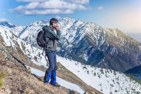 A young man with phone in hand on the top of a snowy mountain far from civilization on a background of blue sky. The concept of activity and the availability of mobile connection