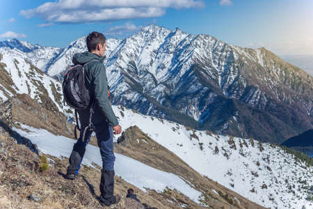 Man Hiker stands on top and looks up at the sky and snowy mountains around in Sunny weather. The concept of travel and achieve the goal 免版税图像