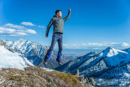 Man tourist hikers in the high jump in the background of snowy mountains. Concept of adventure, freedom and active lifestyle