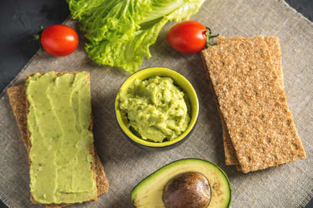 Traditional Mexican cold appetizer made of pureed avocado pulp with bread and vegetables on the table. Concept healthy vegetarian Breakfast Stock Photo