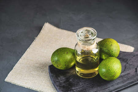 Green avocado fruit and oil in glass bottle on dark background. Concept organic eco products for food and cosmetic procedures