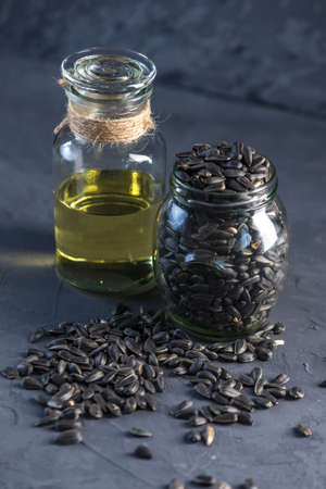 Sunflower seeds in a pile and golden oil in a glass bottle on the table. Concept healthy diet with vegetable fats.