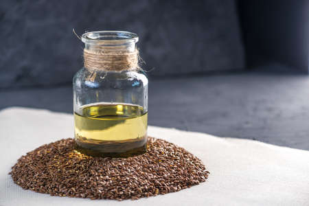 Flax seeds in a pile and linseed golden oil in a glass bottle on the table. The concept healthy diet with omega 3 fatty acids. Zdjęcie Seryjne
