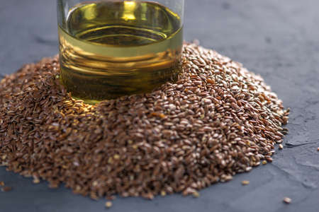 Flax seeds in a pile and linseed golden oil in a glass bottle on the table on a dark background. The concept healthy diet with omega 3 fatty acids. Standard-Bild