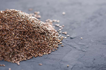 Flax seeds in a pile on a dark background. The concept healthy diet with omega 3 fatty acids.