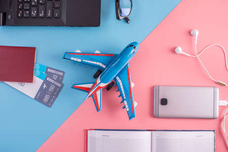 Plane, air tickets, passport, notebook and phone with headphones on pastel background. The view from the top. The concept of planning and preparing for the travel 版權商用圖片