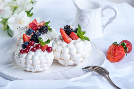 Delicate white meringues with fresh berries on the plate. Dessert Pavlova close-up. White background. A festive wedding cake. Stock Photo