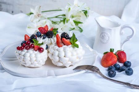 Delicate white meringues with fresh berries on the plate. Dessert Pavlova. White background. A festive wedding cake.