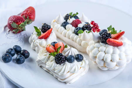 Delicate white meringues with fresh berries on the plate. Dessert Pavlova close-up. White background. A festive wedding cake. 写真素材