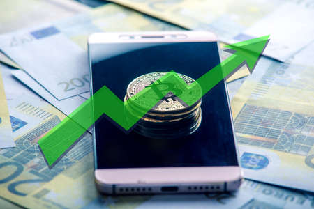 Physical bitcoin coin on the phone screen on the background of the Euro banknotes. Green arrow of the price growth chart Zdjęcie Seryjne