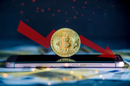 Physical bitcoin coin on the phone screen on the background of the Euro banknotes. Red arrow of the chart of falling quotes down Stock Photo
