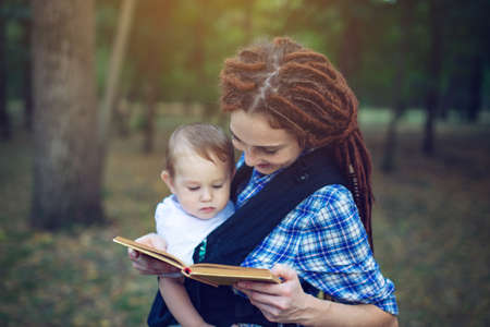 Beautiful mom with a baby in ergo backpack reading a fairy tale in the Park. Children's education in family life Stockfoto