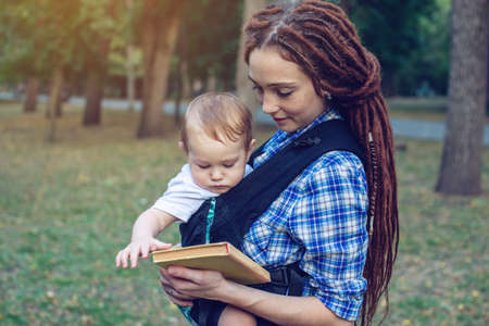 Beautiful mom with a baby in ergo backpack reading a fairy tale in the Park. Children's education in family life Banque d'images
