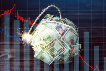 Big bomb of money hundred dollar bills with a burning wick. Little time before the explosion. The concept of financial currency crisis Stock Photo