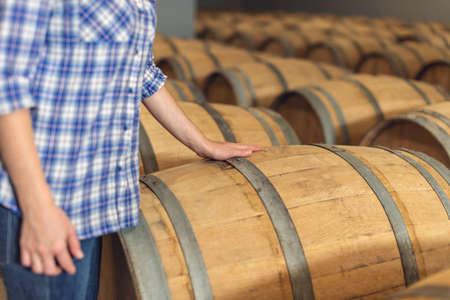 Woman winemaker checks oak wine barrels in which red wine is aged in the basement of the winery. The concept of the production of wine
