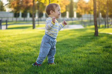Cute baby runs on a green lawn runing in nature on a Sunny autumn day. One-year-old child. The concept first child steps