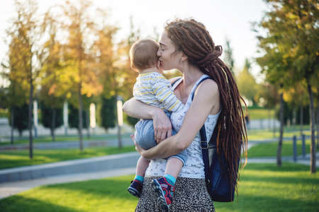 Young modern happy mom with baby son walking in Sunny Park. The concept of the joy of motherhood and autumn mood Stockfoto