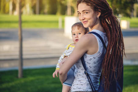 Young modern happy mom with baby son walking in Sunny Park. The concept of the joy of motherhood and autumn mood Stock Photo
