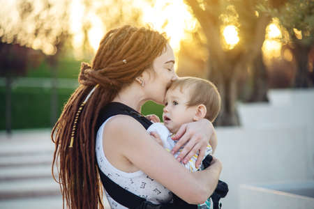 Young modern happy mother with baby son in ergo backpack walking in Sunny summer day. The concept of the joy of motherhood Stockfoto